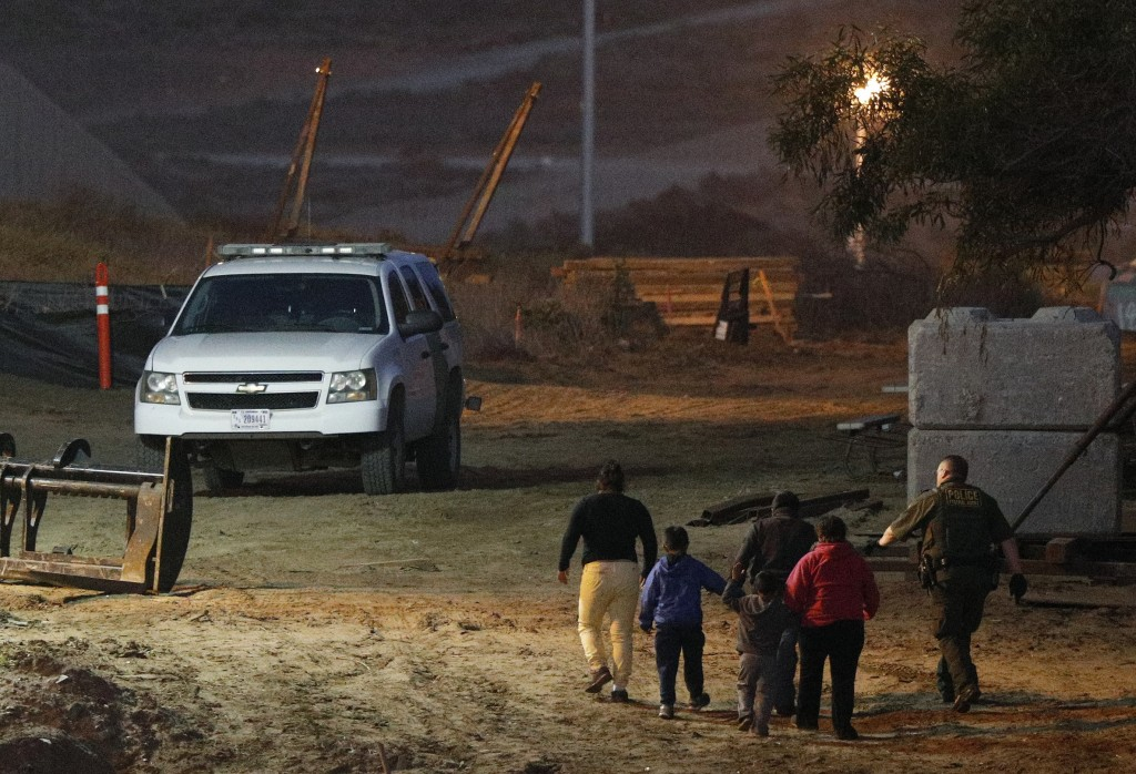 FILE - In this Dec. 3, 2018, file photo, migrants are escorted by a U.S. Border Patrol agent as they are detained after climbing over the border wall ...