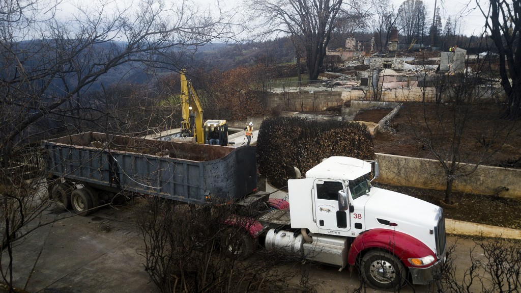 In this Feb. 8, 2019, photo, an excavator loads debris onto a truck while clearing a property burned by the Camp Fire in Paradise, Calif. In the 100 d...