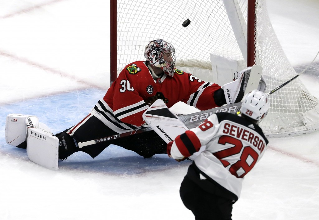Chicago Blackhawks goalie Cam Ward, left, cannot stop a goal by New Jersey Devils defenseman Damon Severson, right, during the first period of an NHL ...