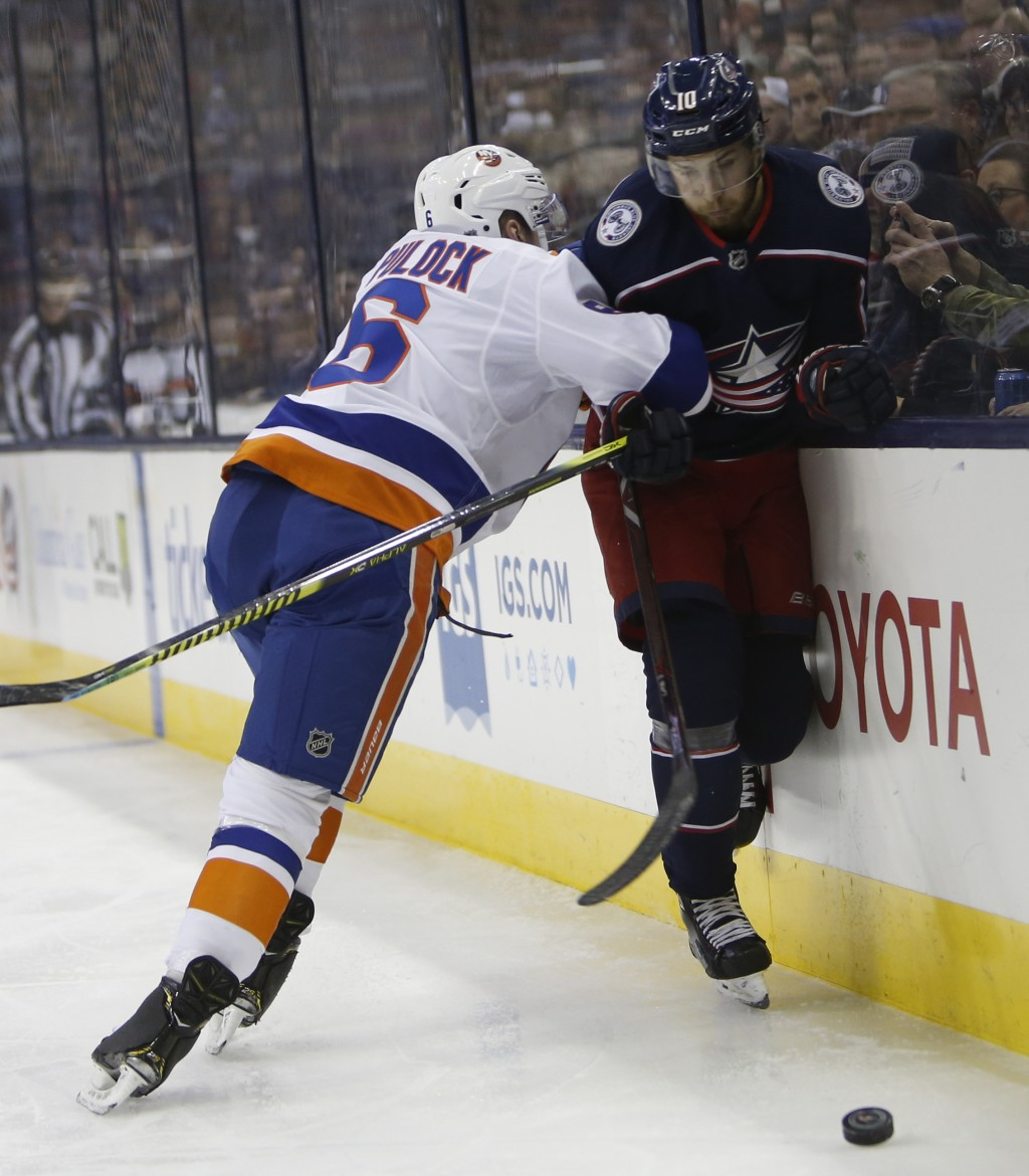 New York Islanders' Ryan Pulock, left, checks Columbus Blue Jackets' Alexander Wennberg, of Sweden, during the second period of an NHL hockey game Thu...