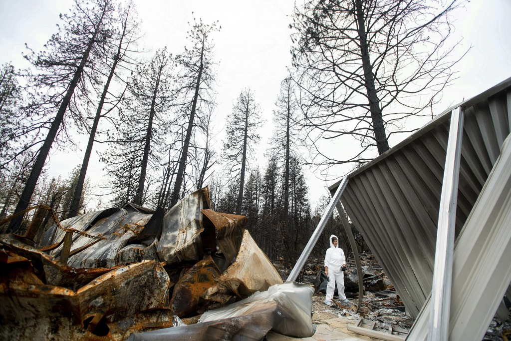 In this Feb. 8, 2019, photo, Carol Mendes-Klint pauses while helping a friend comb through the remains of her residence, destroyed by the Camp Fire, i...