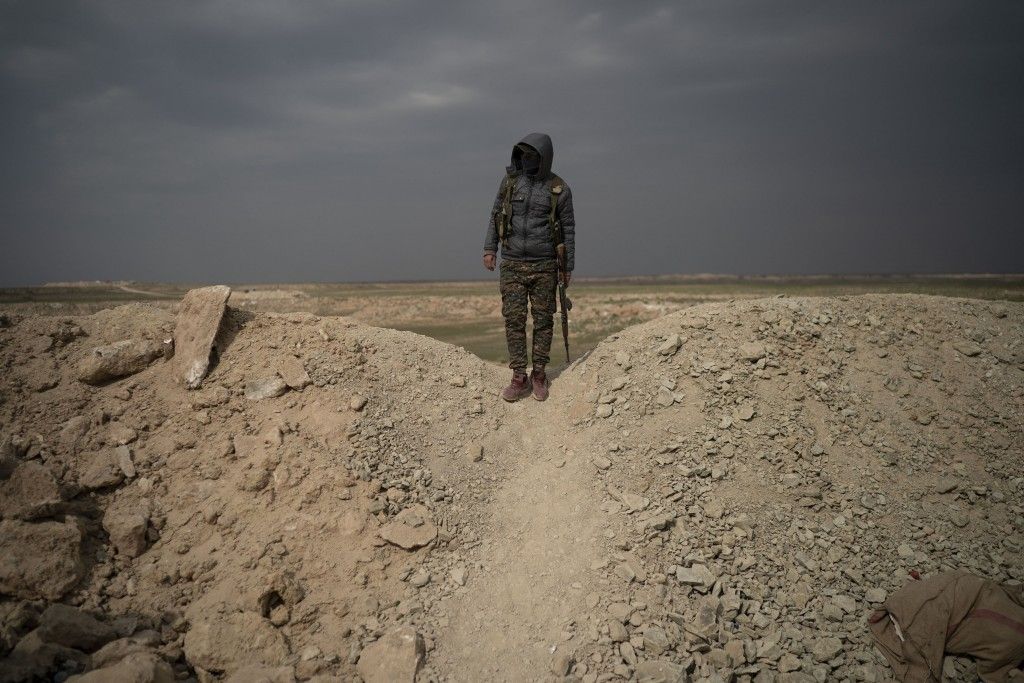 A U.S.-backed Syrian Democratic Forces (SDF) fighter stands atop a hill in the desert outside the village of Baghouz, Syria, Thursday, Feb. 14, 2019. ...