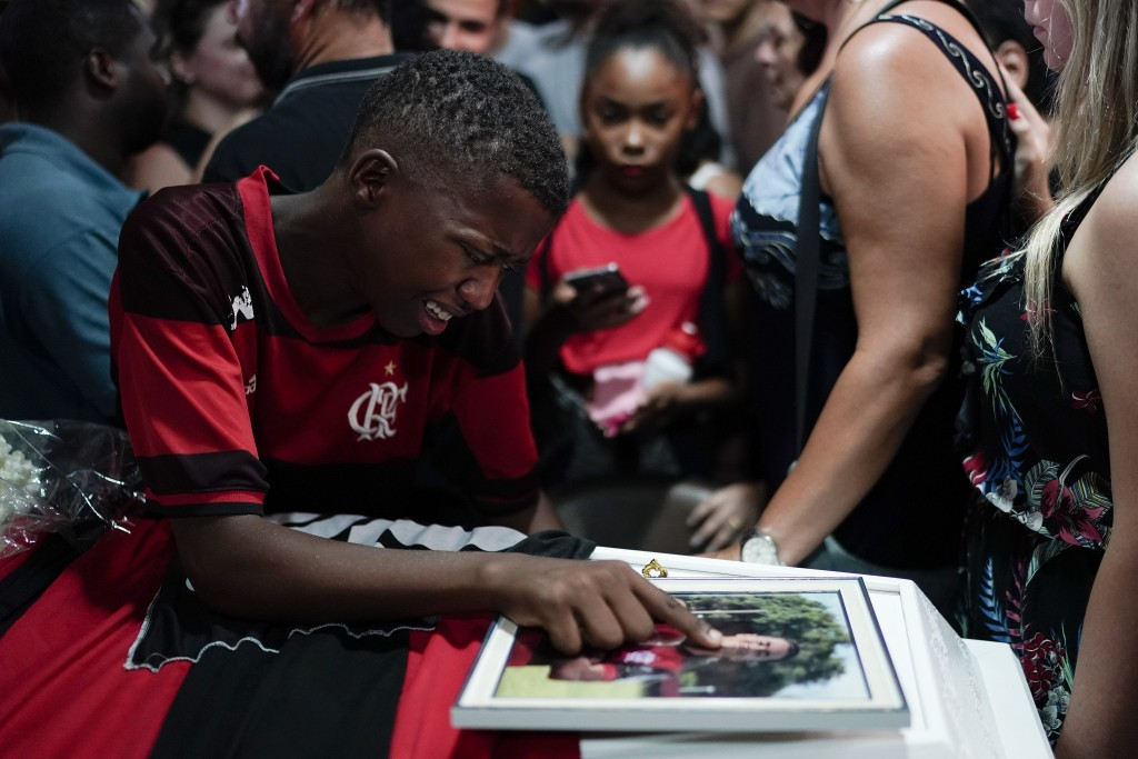 In this Feb. 9, 2019 photo, a friend, wearing a Flamengo soccer kit, grieves over the coffin containing the remains of the young soccer player Arthur ...
