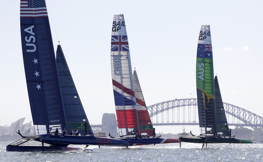Teams from USA, left, Britain and Australia make practice runs with their F50 catamarans ahead of their SailGP race on the harbor in Sydney, Friday, F...