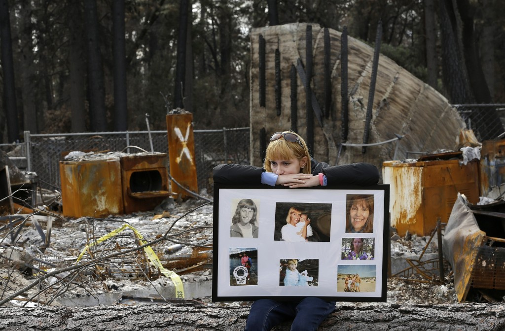 In this Thursday, Feb. 7, 2019 photo, Christina Taft, the daughter of Camp Fire victim Victoria Taft, displays a collage of photos of her mother, at t...