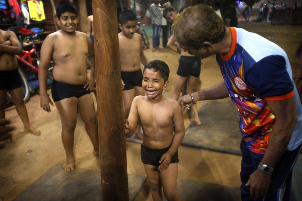 In this Feb 5, 2019, photo, a mallakhamb instructor Sachin Malekar, right, calms a child who made an unsuccessful attempt to climb the pole, at Shivaj...