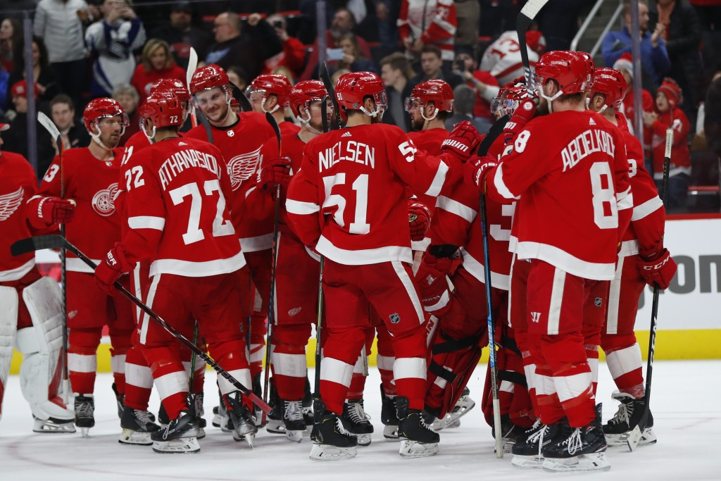 Detroit Red Wings players celebrate their 3-2 win over the Ottawa Senators after an NHL hockey game Thursday, Feb. 14, 2019, in Detroit. (AP Photo/Pau...