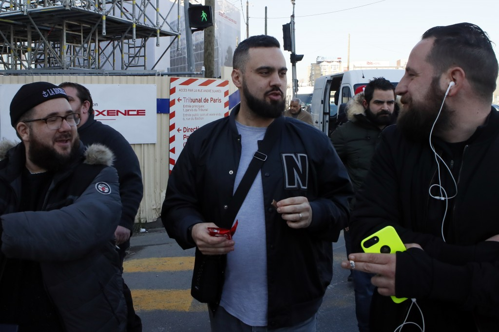 Eric Drouet, center, a prominent and divisive figure of the yellow vest movement, walks out of the Court with his friends after his trial for organizi...