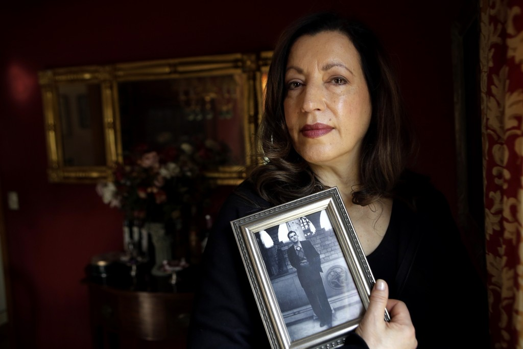 In this Sunday, Feb. 10, 2019 photo, Christina Lamb, daughter of California wildfire victim Julian Binstock, holds a 1950s photo of her father at her ...
