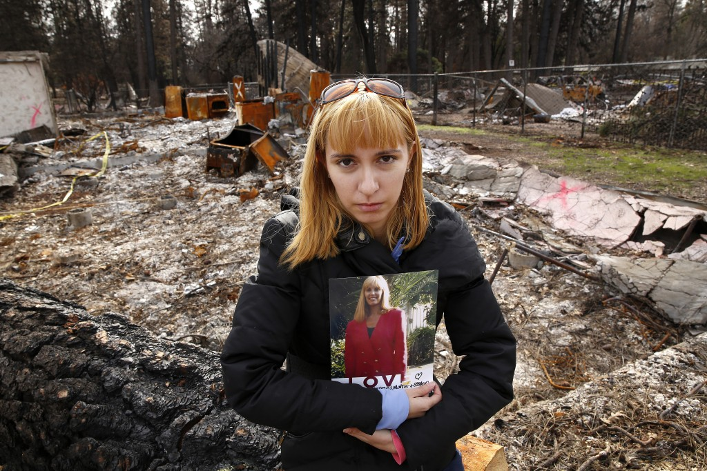 In this Thursday, Feb. 7, 2019 photo, Christina Taft, the daughter of Camp Fire victim Victoria Taft, poses with a photo of her mother, at the burned ...