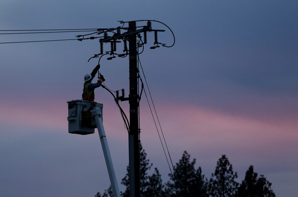 FILE - In this Nov. 26, 2018, file photo, a Pacific Gas & Electric lineman works to repair a power line in fire-ravaged Paradise, Calif. A U.S. judge ...
