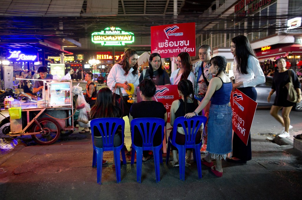 In this Wednesday, Feb. 13, 2019 photo, Pauline Ngarmpring, left, speaks with workers of a roadside massage parlor during an election campaign in Bang...