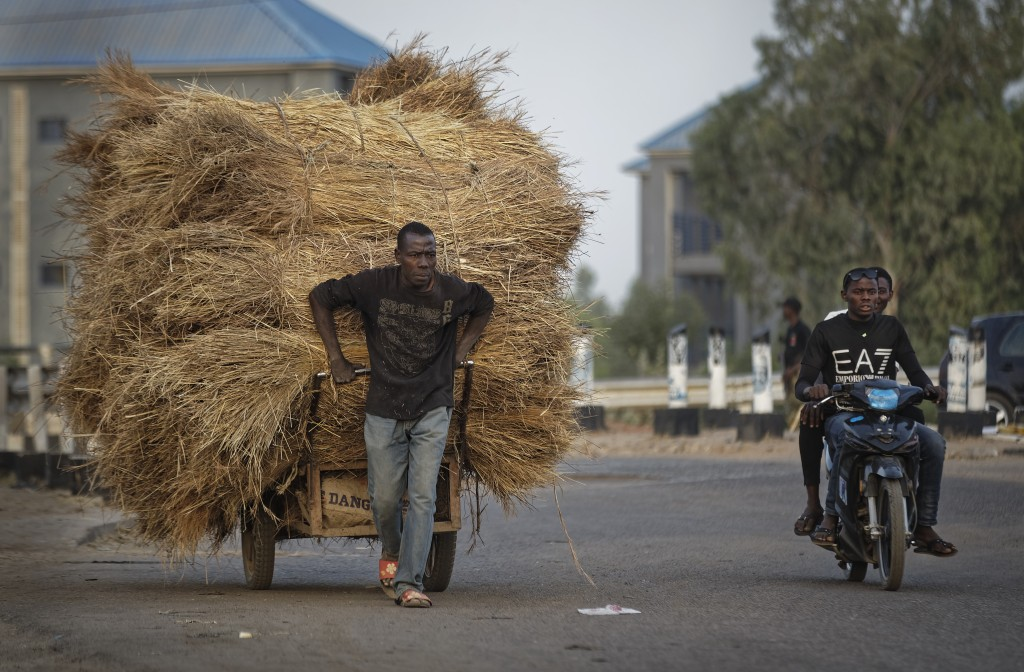 A manual laborer pulls a cart of hay as men drive past on a motorcycle, near the offices of the Independent National Electoral Commission in Kano, nor...