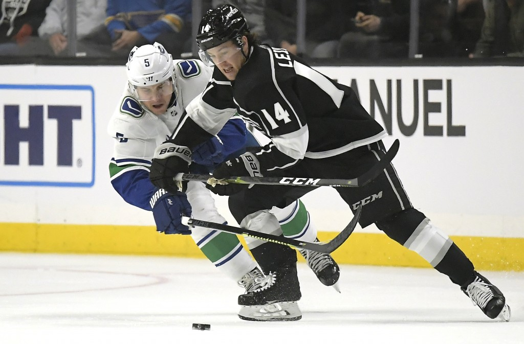 Vancouver Canucks defenseman Derrick Pouliot, left, battles for the puck with Los Angeles Kings left wing Brendan Leipsic during the first period of a...