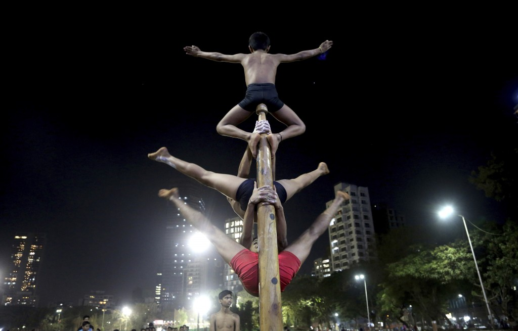 In this Feb. 6, 2019, photo, players perform on a mallakhamb pole at the Shree Samartha Vyayam Mandir at Shivaji Park in Mumbai, India. The word malla...