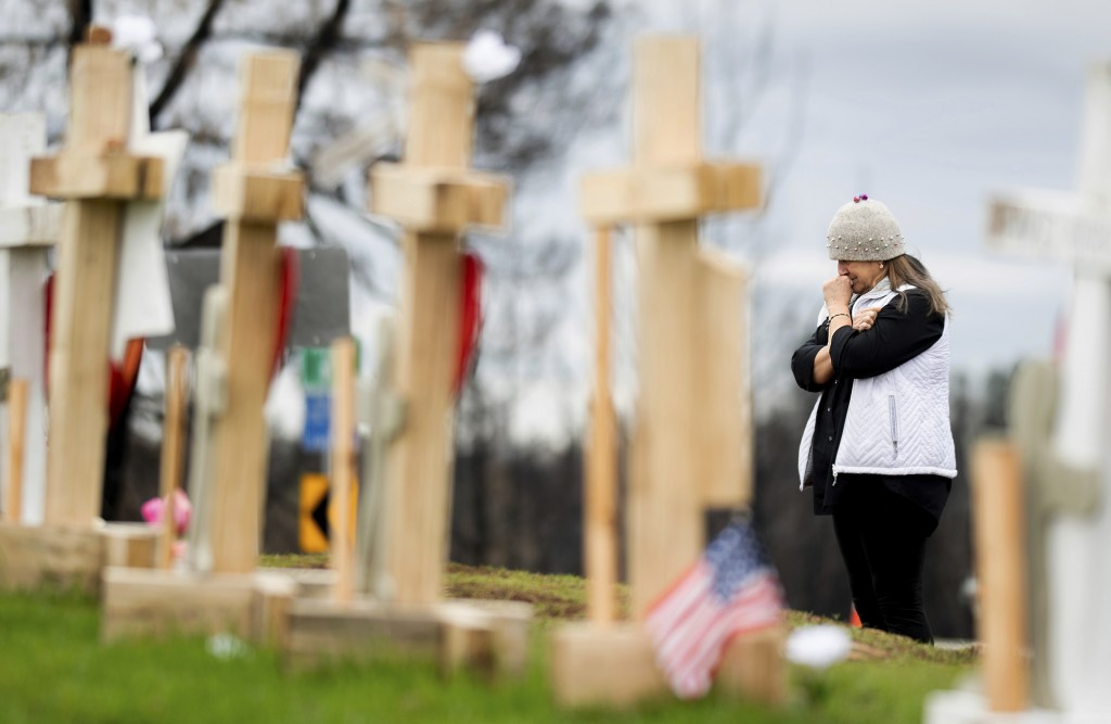 In this Feb. 8, 2019, photo, Joanie Ellison cries while visiting a memorial for Camp Fire victims in Paradise, Calif. Ellison, currently staying on he...