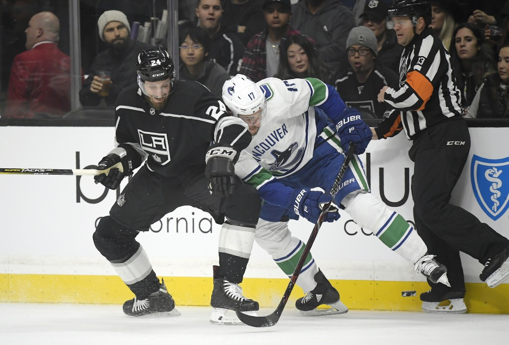 Los Angeles Kings defenseman Derek Forbort, left and Vancouver Canucks left wing Josh Leivo battle for the puck during the first period of an NHL hock...