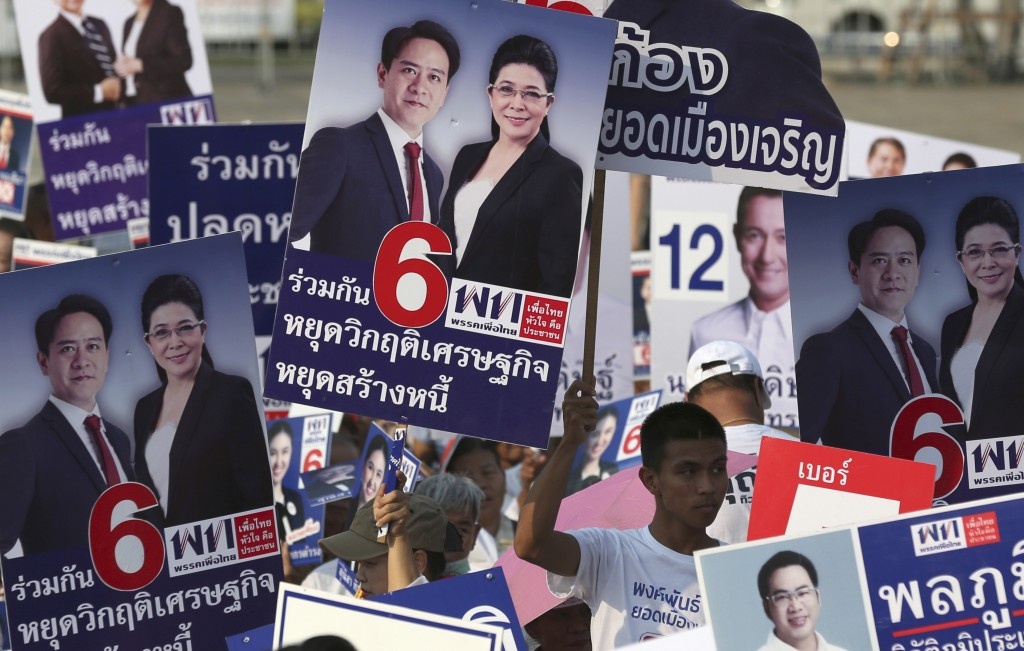 Supporters raise posters of candidates of Pheu Thai Party during an election campaign in Bangkok, Thailand, Friday, Feb. 15, 2019. The nation's first ...