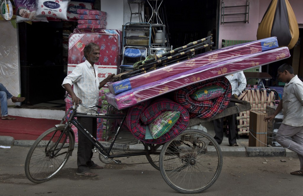 In this Dec. 17, 2018, photo, a cycle rickshaw puller prepares to transport mattresses from the Nampally furniture market in Hyderabad, India. Just 20...
