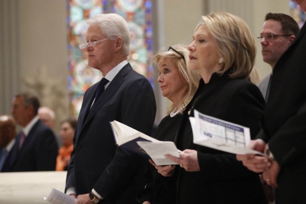 Rep. Debbie Dingell, D-Mich., center, stands with former President Bill Clinton and former Sec. of State Hillary Clinton, during funeral services for ...