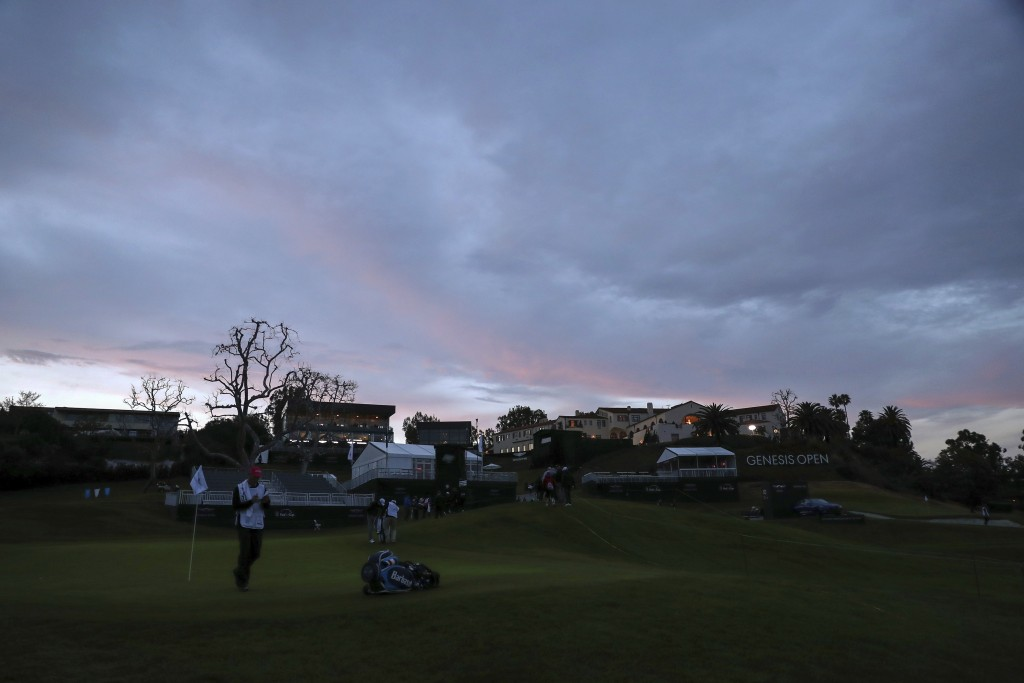 Players and spectators walk to the clubhouse as the sun sets as viewed from the ninth green during the first round of the Genesis Open golf tournament...