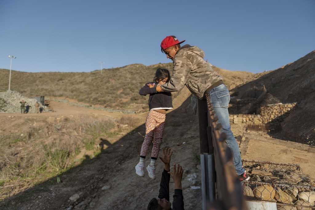 FILE - In this Jan. 3, 2019, file photo, a migrant from Honduras pass a child to her father after he jumped the border fence to get into the U.S. side
