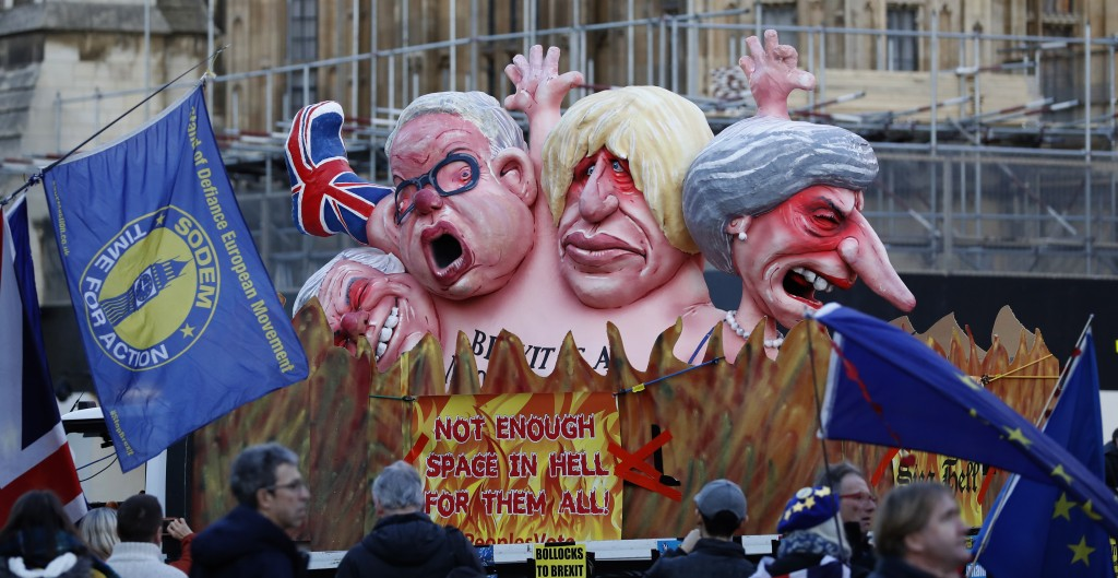 Anti-Brexit demonstrators stand next to a van with large cartoon style portraits of leading British politicians including, from right, Prime Minister ...