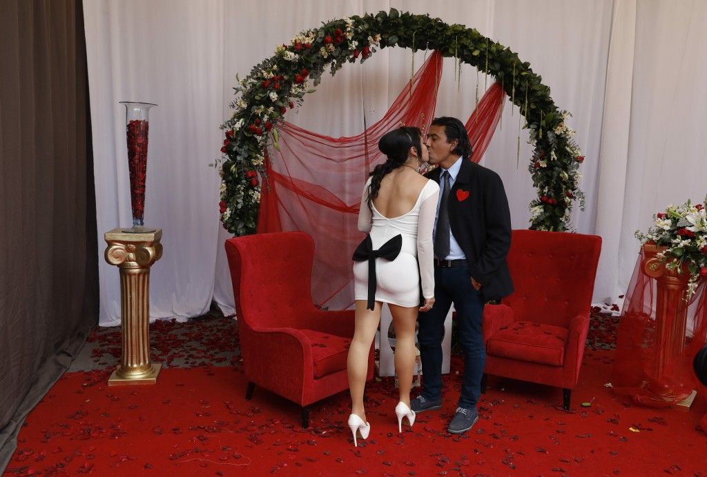 In this Feb. 14, 2019 photo, a newlywed couple kisses while posing for photos at one of several free sets placed for newlyweds to take cell phone phot...