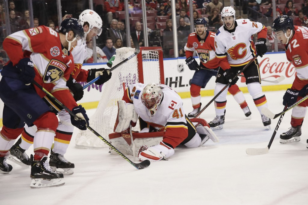Calgary Flames goaltender Mike Smith catches the puck in front of Florida Panthers center Aleksander Barkov during the first period of an NHL hockey g...