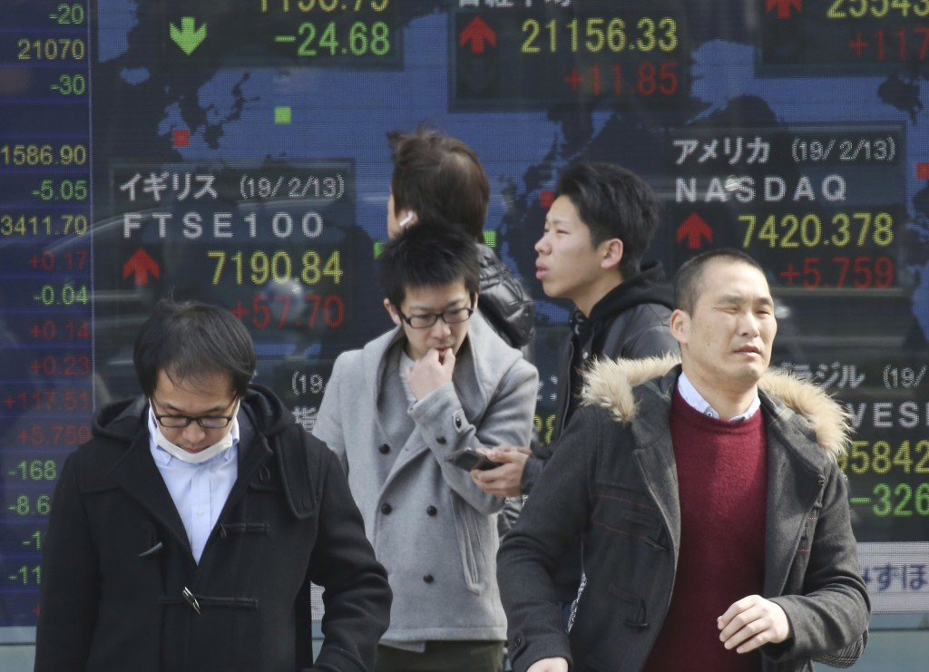 In this Thursday, Feb. 14, 2019, photo, people walk by an electronic stock board of a securities firm in Tokyo. Asian shares were broadly lower on Fri...