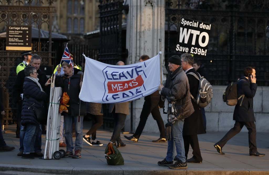 Pro Brexit demonstrators hold banners and placards outside an entrance to the Palace of Westminster in London, Thursday, Feb. 14, 2019. British lawmak...