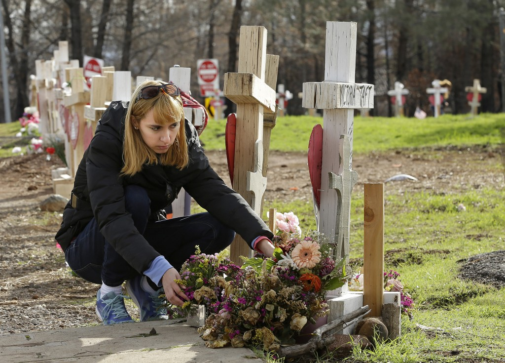 In this Thursday, Feb. 7, 2019 photo, Christina Taft, the daughter of Camp Fire victim Victoria Taft, arranges flowers she had previously left at a cr...