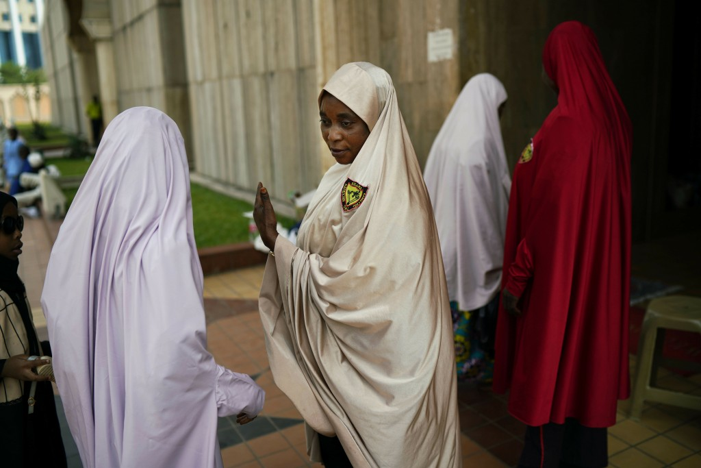 A Nigerian woman attending Friday prayers at the central mosque is security checked a day prior to the election, in Abuja, Nigeria, Friday Feb. 15, 20...