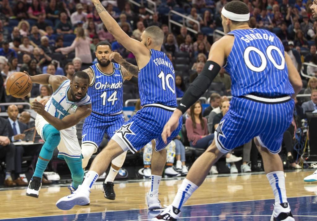 Charlotte Hornets guard Kemba Walker (15) dribbles against Orlando Magic guard D.J. Augustin (14), guard Evan Fournier (10) and forward Aaron Gordon (...