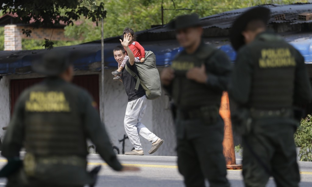 In this Feb. 7, 2019 photo, a Venezuelan migrant waves at Colombian police as he walks past in Los Patios, near Cucuta, Colombia. Humanitarian assista...