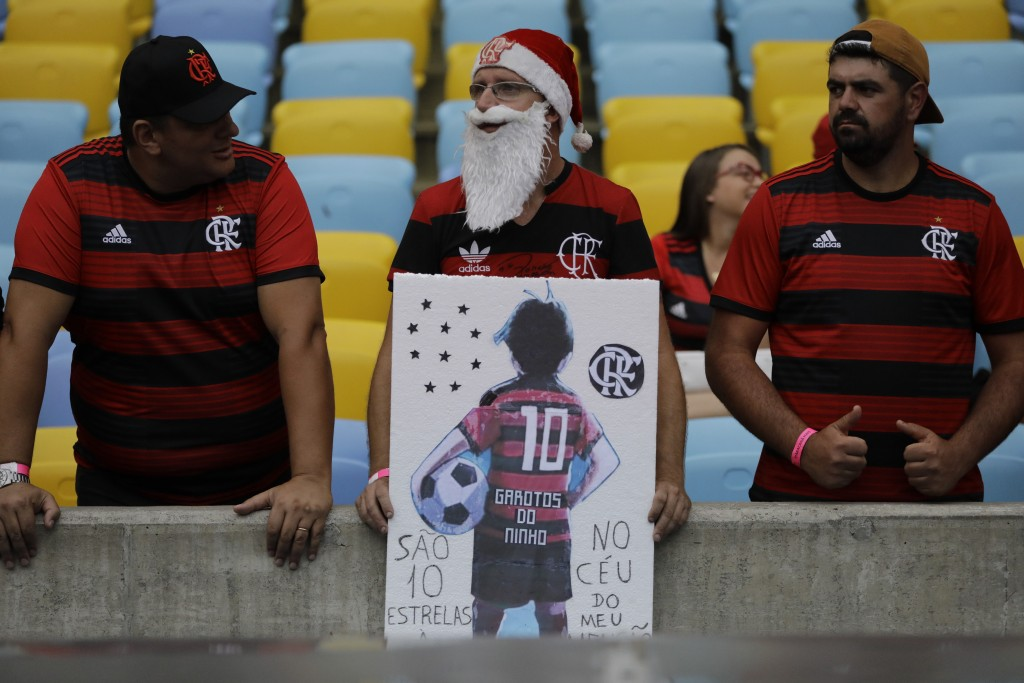 A man holds a drawing of a teenager in a Flamengo kit, as he waits for the start of a homage for the 10 teenage players killed by a fire at the Flamen...