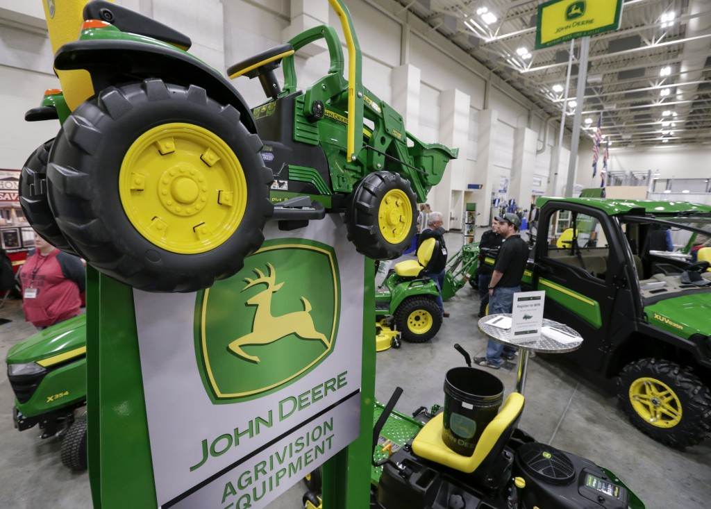 """FILE - In this Feb. 23, 2018 file photo, John Deere products, including a toy tractor on the sign, are on display at the """"Spring into Spring"""" home and..."""