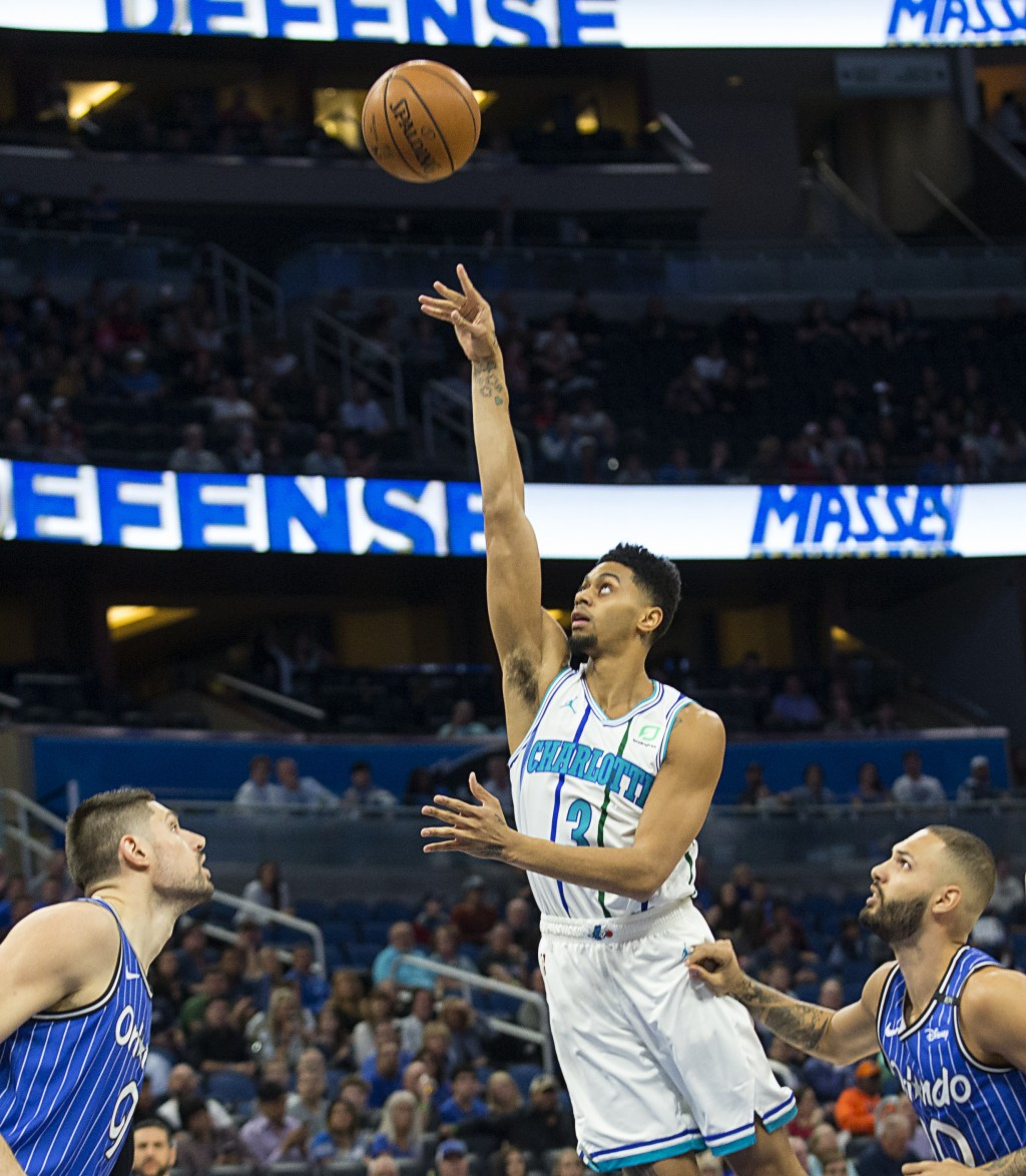 Charlotte Hornets guard Jeremy Lamb (3) shoots over Orlando Magic center Nikola Vucevic (9) and guard Evan Fournier (10) during the first half of an N...