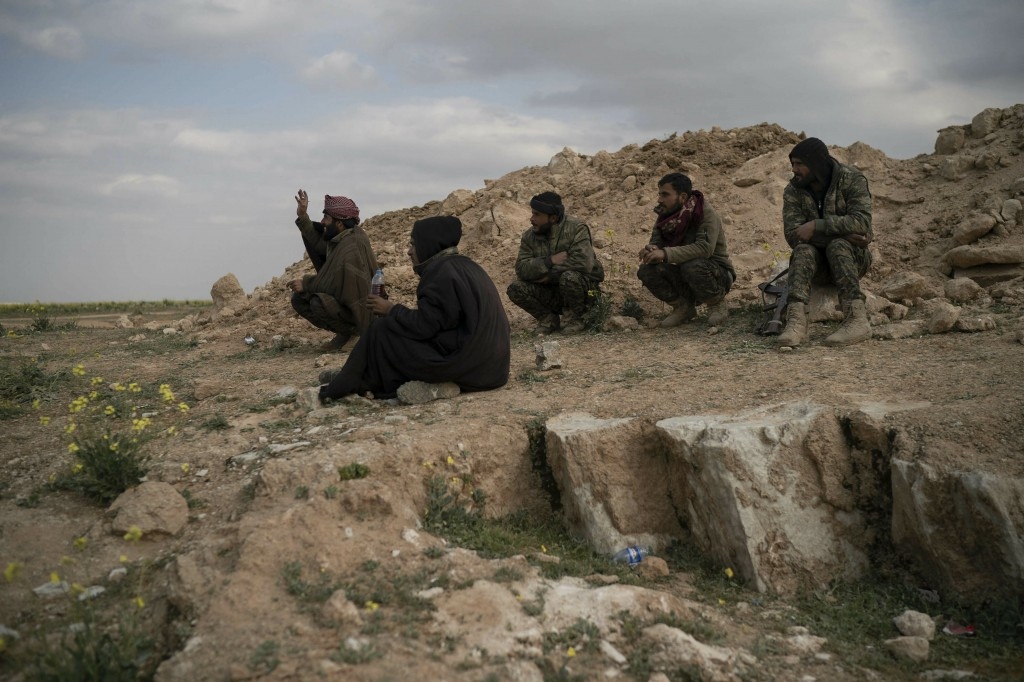 U.S.-backed Syrian Democratic Forces (SDF) fighters sit atop a hill in the desert outside the village of Baghouz, Syria, Thursday, Feb. 14, 2019. U.S....