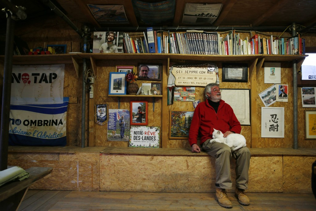 Guido Fissore, activist of the No-TAV movement, sits with his cat at the movement's headquarters in Venaus, northern Italy, Tuesday, Feb. 12, 2019. Th...