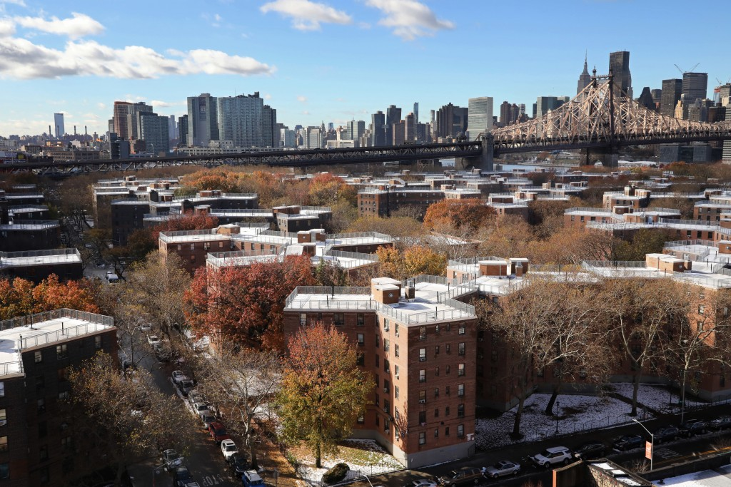 FILE- In this Nov. 16, 2018, file photo the Queensbridge Houses sit beneath the Ed Koch Queensboro Bridge, upper right, in New York. According to expe...