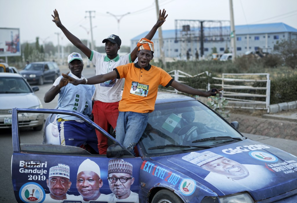 Youth supporters of President Muhammadu Buhari cheer as they return from a rally of the ruling All Progressives Congress party, near the offices of th...