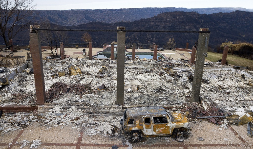 FILE - In this Dec. 3, 2018, file photo, a vehicle rests in front of a home leveled by the Camp Fire in Paradise, Calif. Two statewide officials want ...