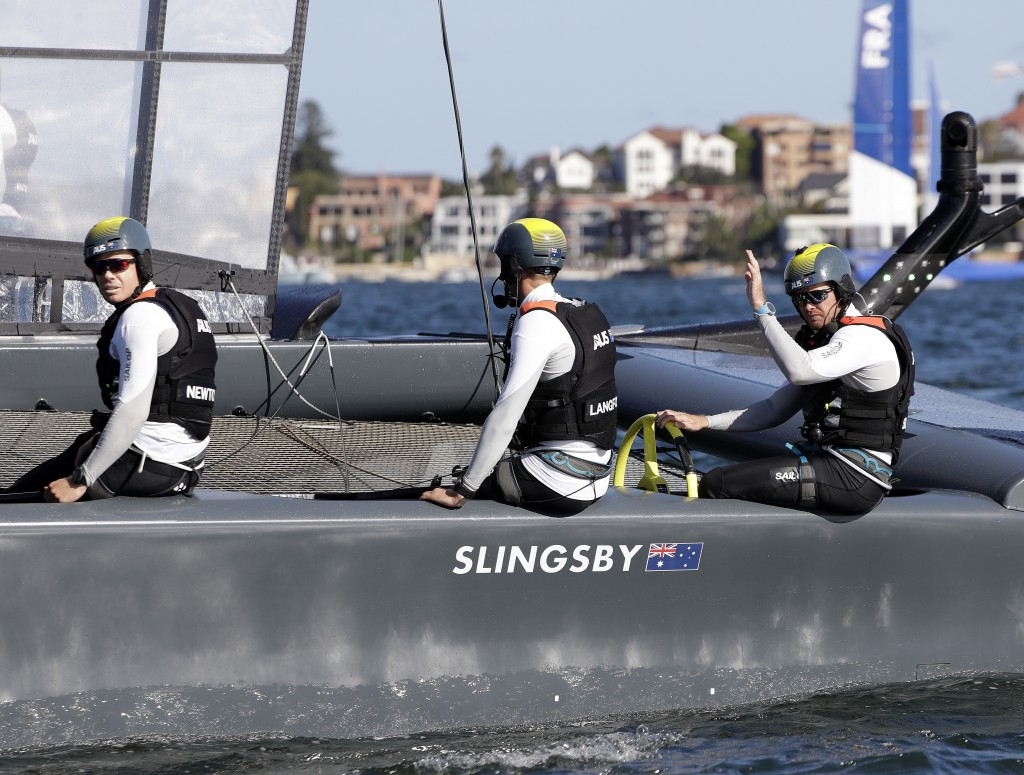 The Australian helmsmen Tom Slingsby, right, waves after winning a race in their F50 catamaran during their SailGP race on the harbor in Sydney, Frida...