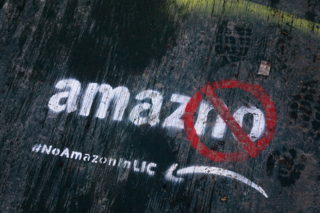 FILE- In this Nov. 16, 2018, file photo graffiti has been painted on a sidewalk by someone opposed to the location of an Amazon headquarters in the Lo...