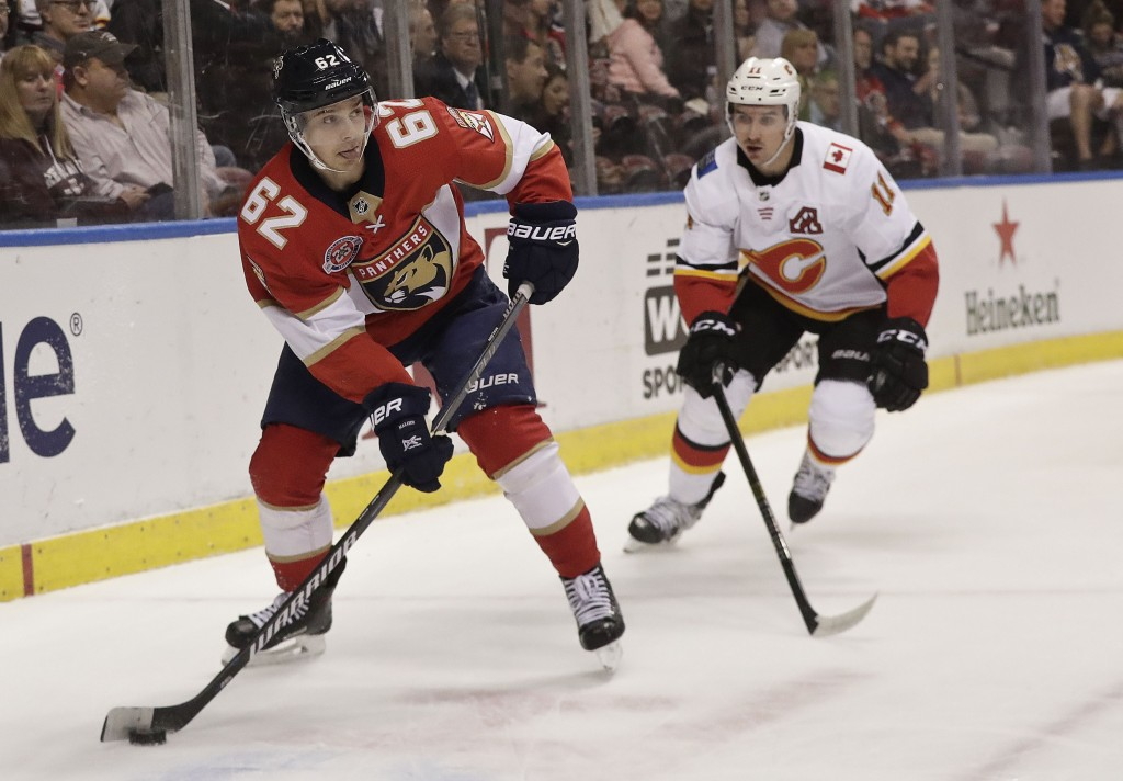 Florida Panthers center Denis Malgin skates with the puck against Calgary Flames center Mikael Backlund during the first period of an NHL hockey game ...