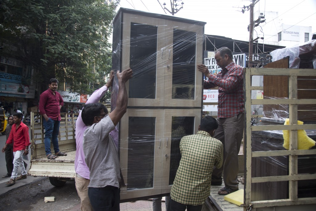 In this Dec. 17, 2018, photo, workers unload a wardrobe from a truck at the Nampally furniture market in Hyderabad, India. This furniture market, wher...