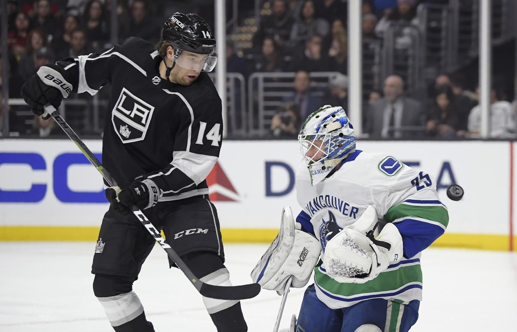 Los Angeles Kings left wing Brendan Leipsic, left, watches the puck fly past Vancouver Canucks goaltender Jacob Markstrom without going in the net dur...