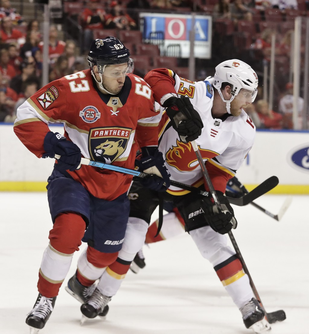 Florida Panthers right wing Evgenii Dadonov and Calgary Flames center Sam Bennett both go for the puck during the second period of an NHL hockey game ...
