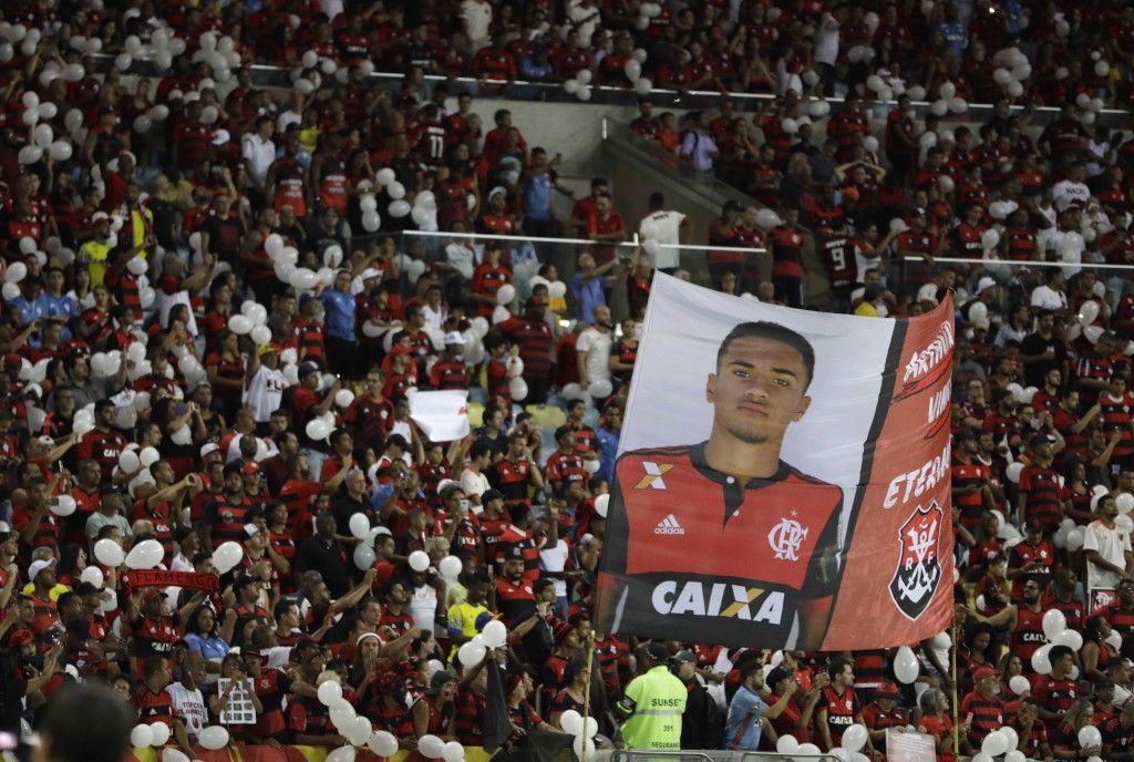 Fans hold up a banner that shows Arthur Vinicius, one of the 10 teenage players killed by a fire at the Flamengo training center last Friday, during a...